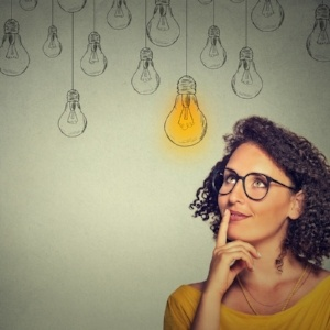 Thinking woman in glasses looking up with light idea bulb above head isolated on gray wall background-603464-edited.jpeg